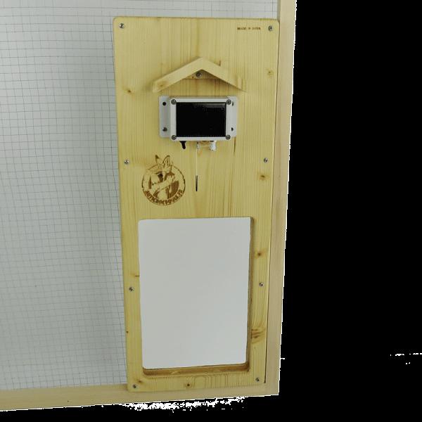Porte automatique solaire en bois fixée sur du grillage